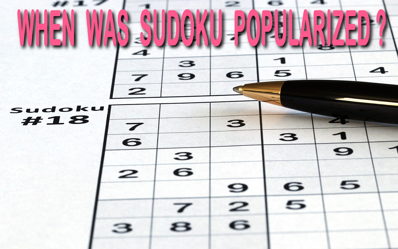 'When Was Sudoku Popularized' pink title on a background picture of an unsolved sudoku puzzle and a pen