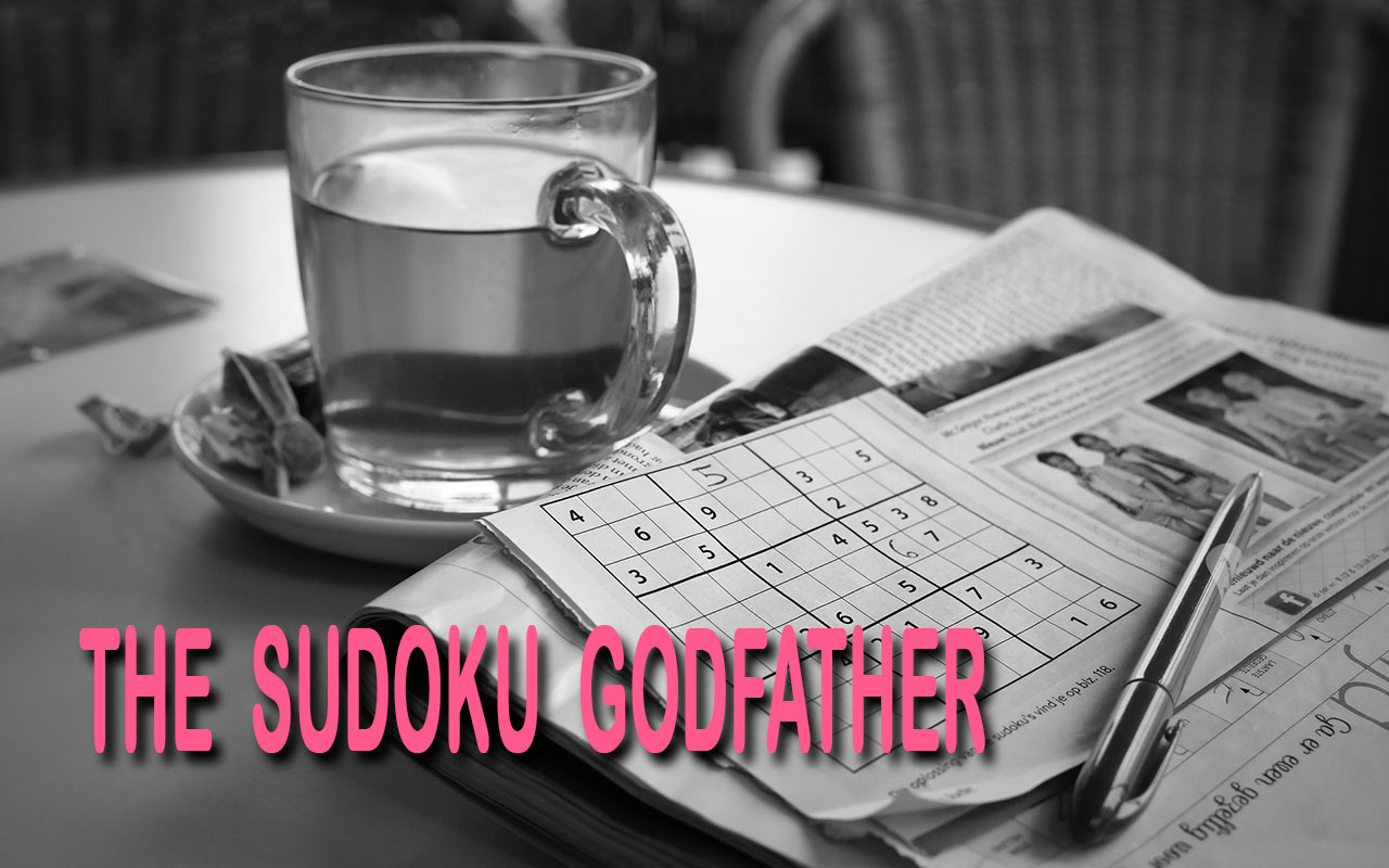 A table with tea mug and a stack of Sudoku newspaper with a pen on top of them