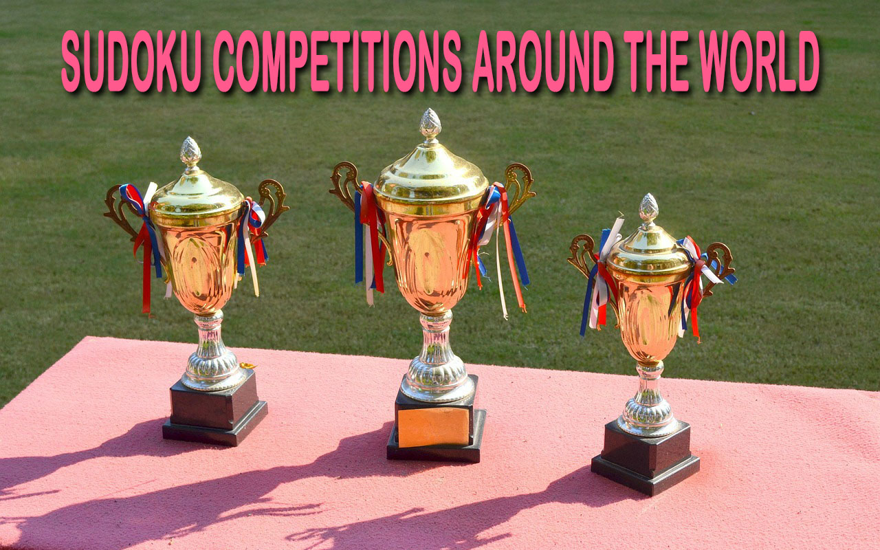 Three golden trophies with blue white and red ribbons sitting on a competition table at the sudoku world championship